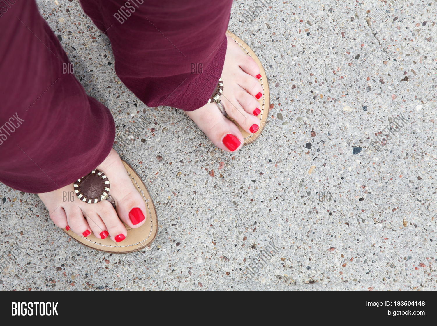 0b46e81af72b28 feet of a caucasian woman wearing red nail-polish and flip-flops