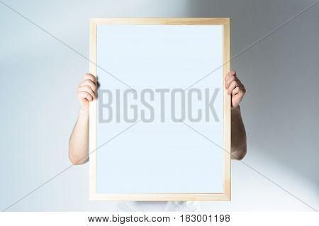 man hold Wood frame mock up, in home room design