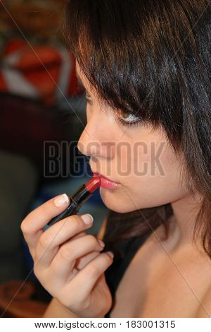 Lovely young brunette applying lipstick, against a dark back ground