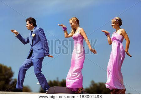Funny groom with the two bridesmaids on the street