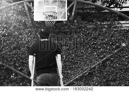 Man Standing With Broken Leg In Plaster Cast Using Crutches At Basketball Court