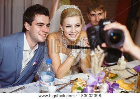 Newlyweds are watching photos on the wedding party