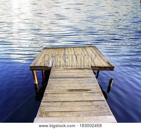 Pier on a blue calm lake, summer background