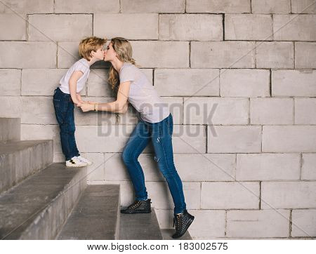 Mother and son standing on a stairs