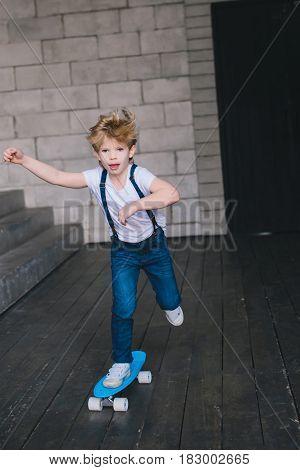 Little boy skate on the blue skateboard