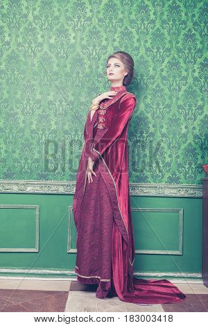 Woman in rich vintage interior and retro rococo clothes. Luxury and high class