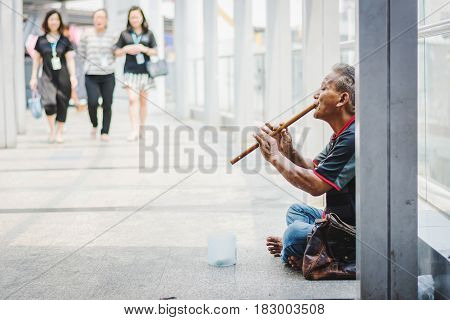 BangkokThailand - 28 Feb 2017: beggar man with flute begging for money on the street