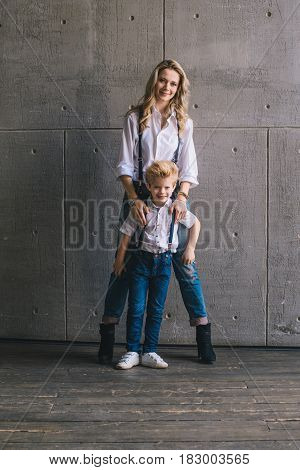 Mother hugging with son hugging and standing at a wall
