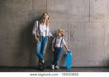 Mother and son with a skateboard standing at a wall