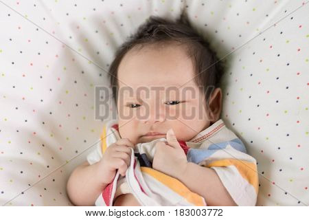 Cute Asian Baby Laying On Bed,