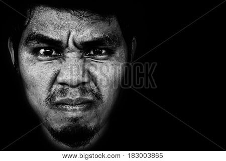 Close-up image of angry face of man on black background