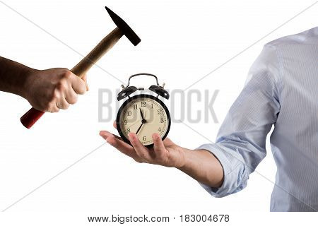Man holding an alarm clock that is broken by a hammer
