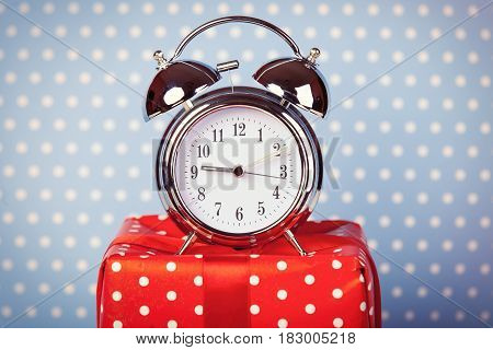 photo of alarm clock and cute gift on the wonderful dotted background in pop art style