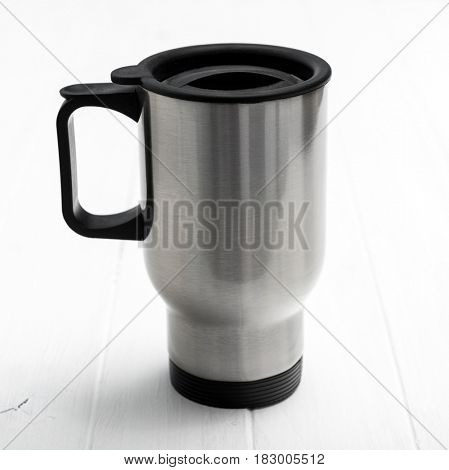 Huge lovely metallic thermocup with black comfortable handle on side, sitting on table