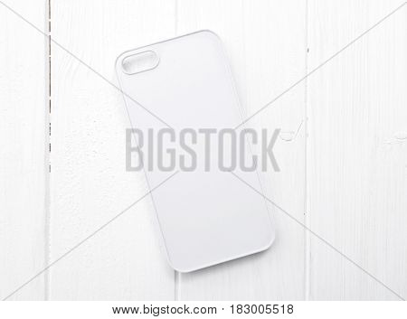 White case for printing, simple and modern design, lying on white wooden table, topview