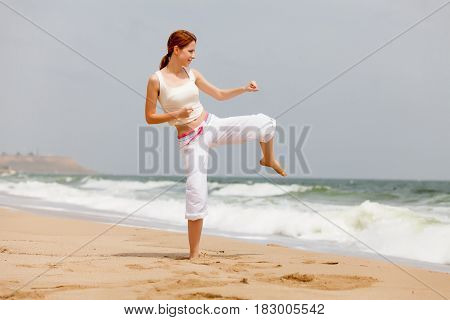 photo of beautiful young woman doing joga on the wonderful see and sky background