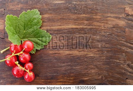 Red currants with leaves on a wooden background.