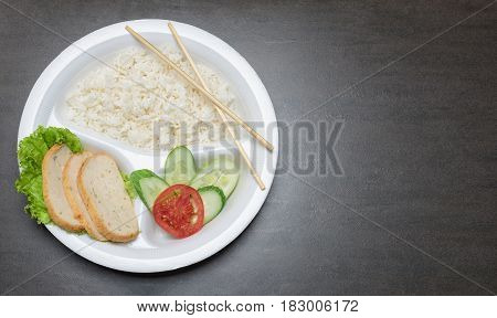 Disposable plastic food plate on black table. White plate with rice meat and vegetables. Bamboo chopsticks. Healthy take-away concept