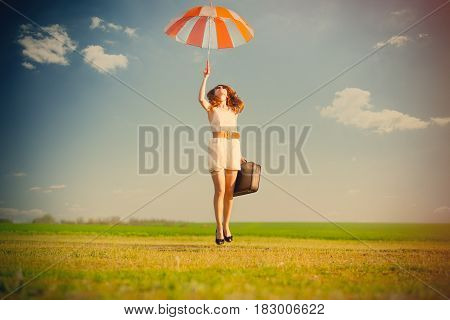 Photo Of Beautiful Young Woman With Suitcase And Umbrella On The Wonderful Field Background