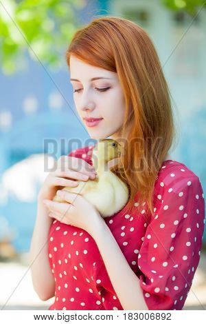 portrait of beautiful young woman with duckling on the wonderful trees and building background