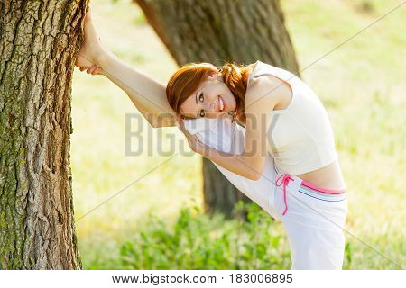 portait of beautiful young woman doing joga on the wonderful trees background