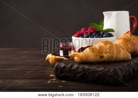 Delicious breakfast with fresh croissants and ripe berries on old wooden background. Healthy food concept with copy space. Dark photo.