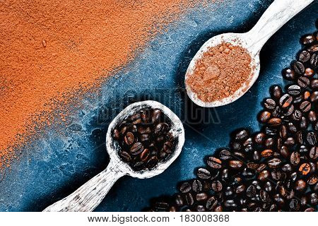 Cocoa powder and coffee beans scattered and partly covering black slate background. Rustic wooden spoons full of cacao powder and coffee beans. Top view