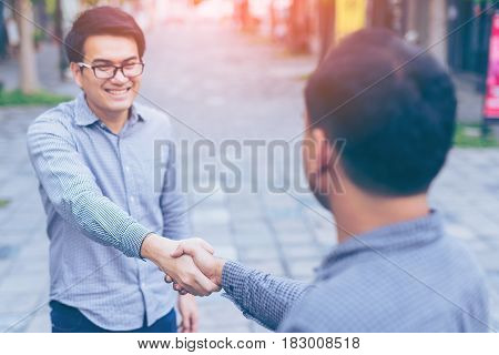 Men shaking hands. Sealing a deal! Two happy young asian businessman shaking hands while standing on the paving tiles cement brick floor. Focus on hands