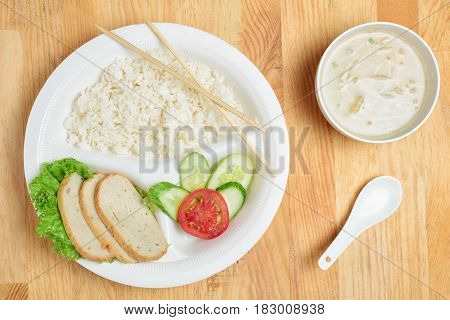 Disposable plastic food plate on wooden table. White plate with rice meat and vegetables. Soup with sprouts. Spoon and bamboo chopsticks. Healthy take-away concept