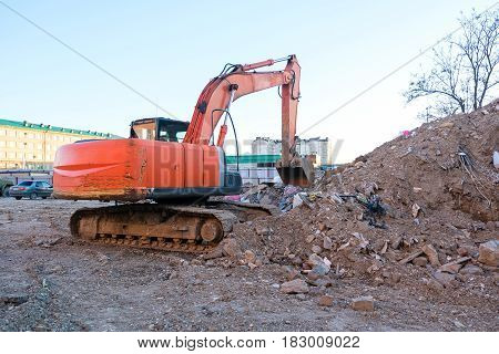 Excavator working on the excavation works of a road, moving rock and earth.