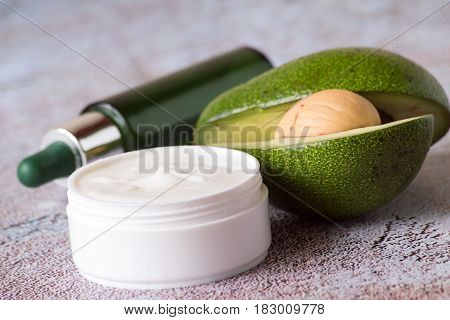 Cosmetic means for skin care based on fruits of avocado. A jar with nutritious cream for the face and a bottle with serum.
