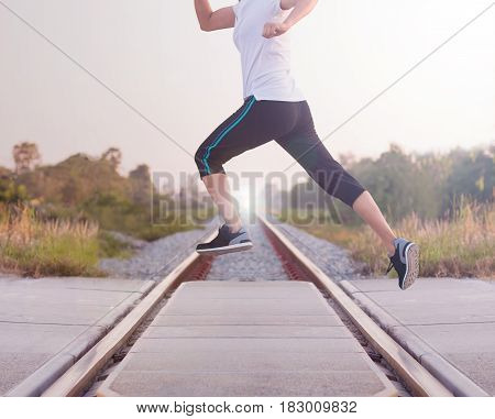 Young woman jumping above the railway during the jogging Healthy lifestyle and sport concepts.