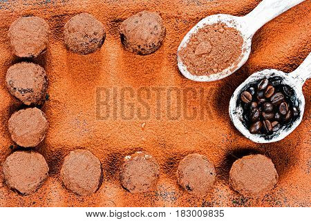 Homemade chocolate truffles on cocoa powder background. Rustic wooden spoons full of cacao powder and coffee beans. Top view