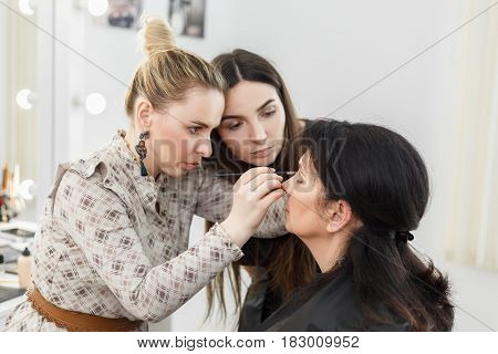 visagiste applying makeup on the eyes. Professional makeup teacher training her student girl to become makeup artist. Lesson at beauty school. Master class.  Explaining how to apply makeup properly
