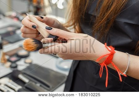 woman makeup artist applying concealer on hand. Closeup visagiste applying foundation on hand. Female hand testing foundation
