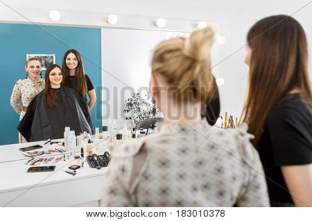 reflection in the mirror satisfied client with ready makeup in beauty salon. Backstage photo. Result of makeup master class. Happy customer and makeup artist