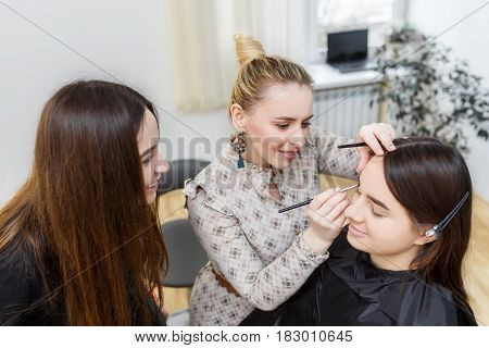makeup teacher with her student girl. Makeup tutorial lesson at beauty school. Visagiste applying makeup on the eye. Makeup master class