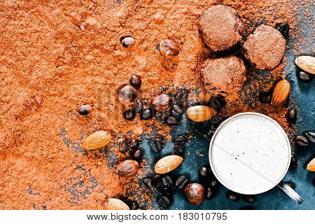 Cocoa powder scattered on black slate with homemade chocolate truffles, coffee beans and nuts. Cup of cacao drink. Top view
