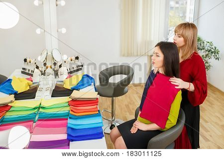 stylist performs personal color analysis consultation for woman. Color type test. Image maker determines the colors that best suit an individual based on client natural colorings. Color classification