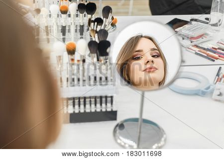 reflection in the mirror girl with glamorous makeup in beauty salon. Backstage photo. Beautiful woman looking in the mirror after applying makeup. Client checks makeup. Photo with selective focus