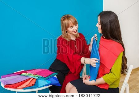 color analysis consultation. Color type test. Stylist determines the colors that best suit an individual based on client natural colorings. Smiling image maker works with young woman