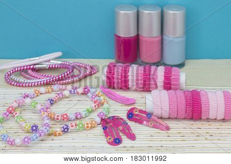 Girlish teenager room place for makeup at home. A group of three colorful Nail Polish bottles hair ribbons bracelets necklaces hair clips. Vintage style background