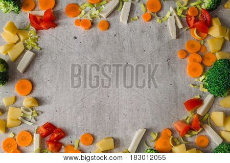 Frame of juicy sliced vegetables on gray stone background. Carrots, broccoli, parsley root, leek, tomato, potatoes are so appetizing and useful.