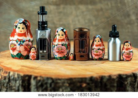 Matryoshka Family And E-cigarette. Vaping Things And Russian Doll On A Wooden Table. Russia Vape. Ma