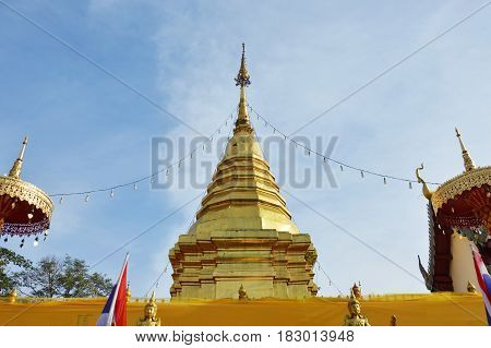 golden pagoda contain Buddha ash entwined praying cloth in Wat Phrathat Doi Kham ancient temple in Thailand
