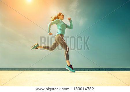 Woman running along the sealine coast under sunlight at sunny summer day.