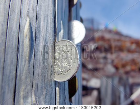 FUJI MOUNTAIN Japan. 2016 August 28 100 yen coin was plugged on the wooden pole rift of the gate to the vertex of FUJI Mountain. This is a faith which good things will coming into their life.