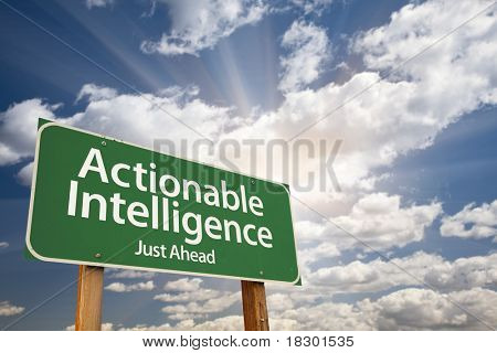 Actionable Intelligence Green Road Sign on Dramatic Blue Sky with Clouds.