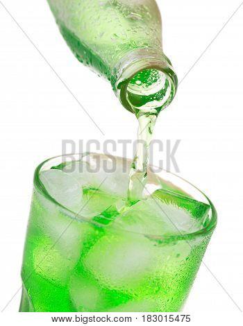 Pouring Green Soda Into Glass With Ice From Bottle