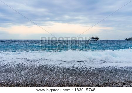 View of the sea with soft gentle waves with foam in the evening summer vacation